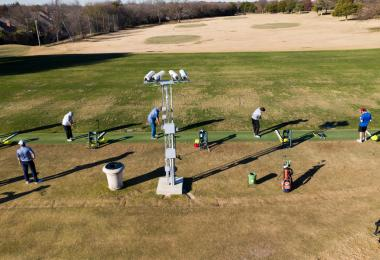 Golfers line up to practice their shots at a driving range.
